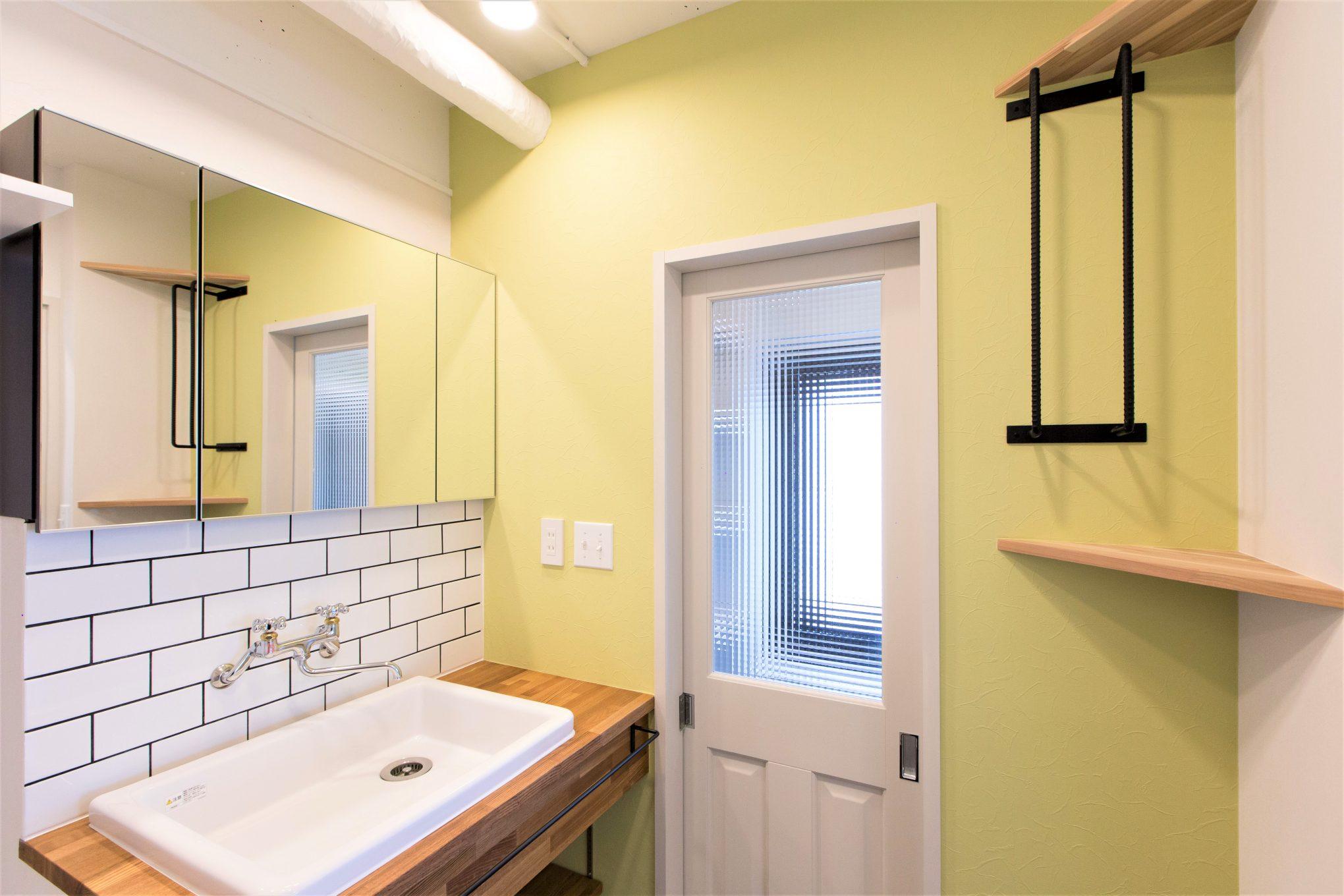 洗面台も木で造作。壁紙は他室と変えてパステルイエローに