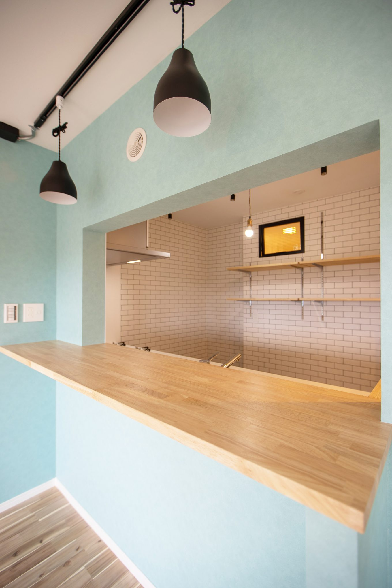 ブルーの壁にホワイトのサブウェイタイルがおしゃれなキッチン