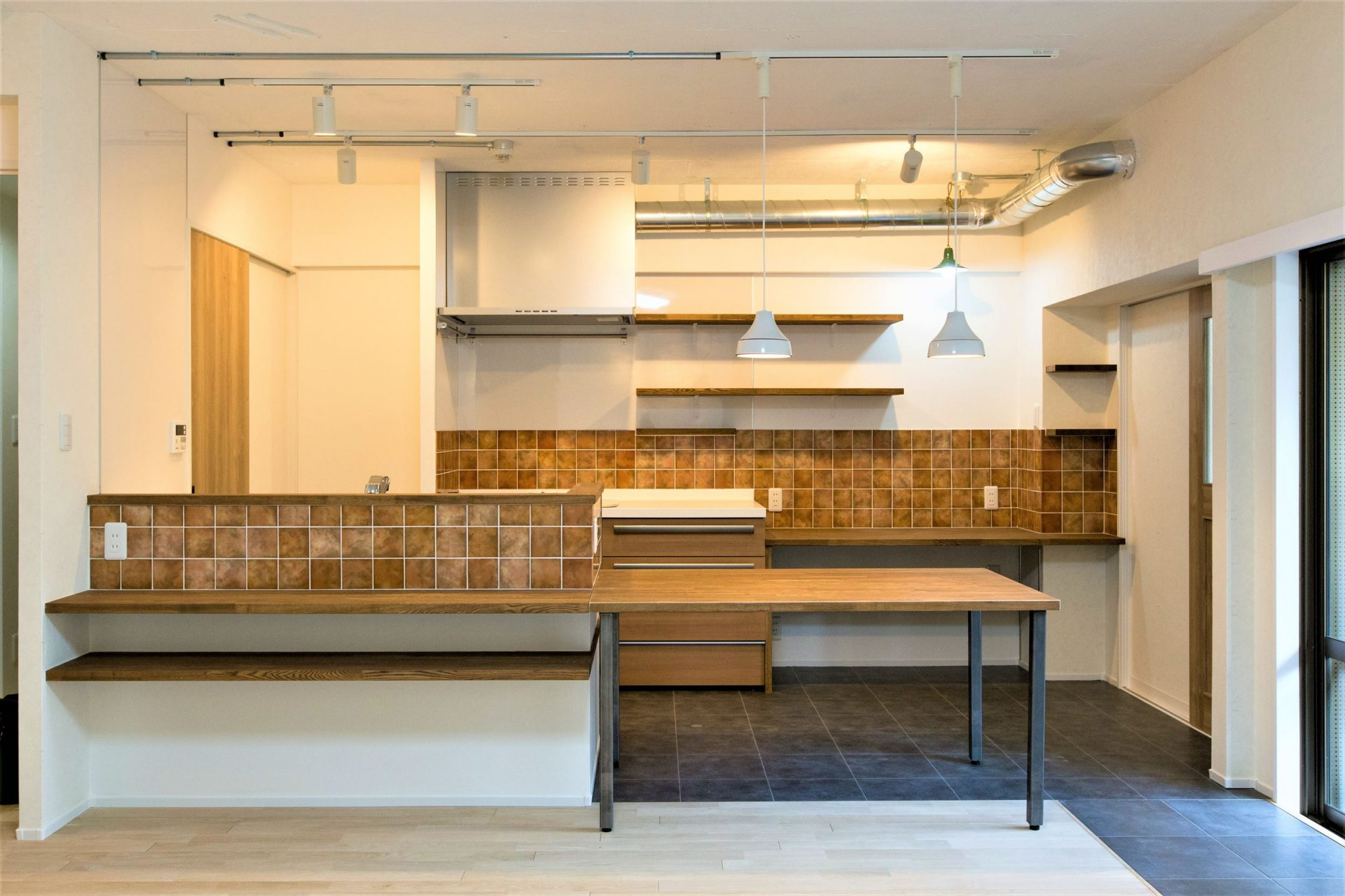 シンクと作業台兼ダイニングテーブルを造作し、リビングに向けたキッチン。