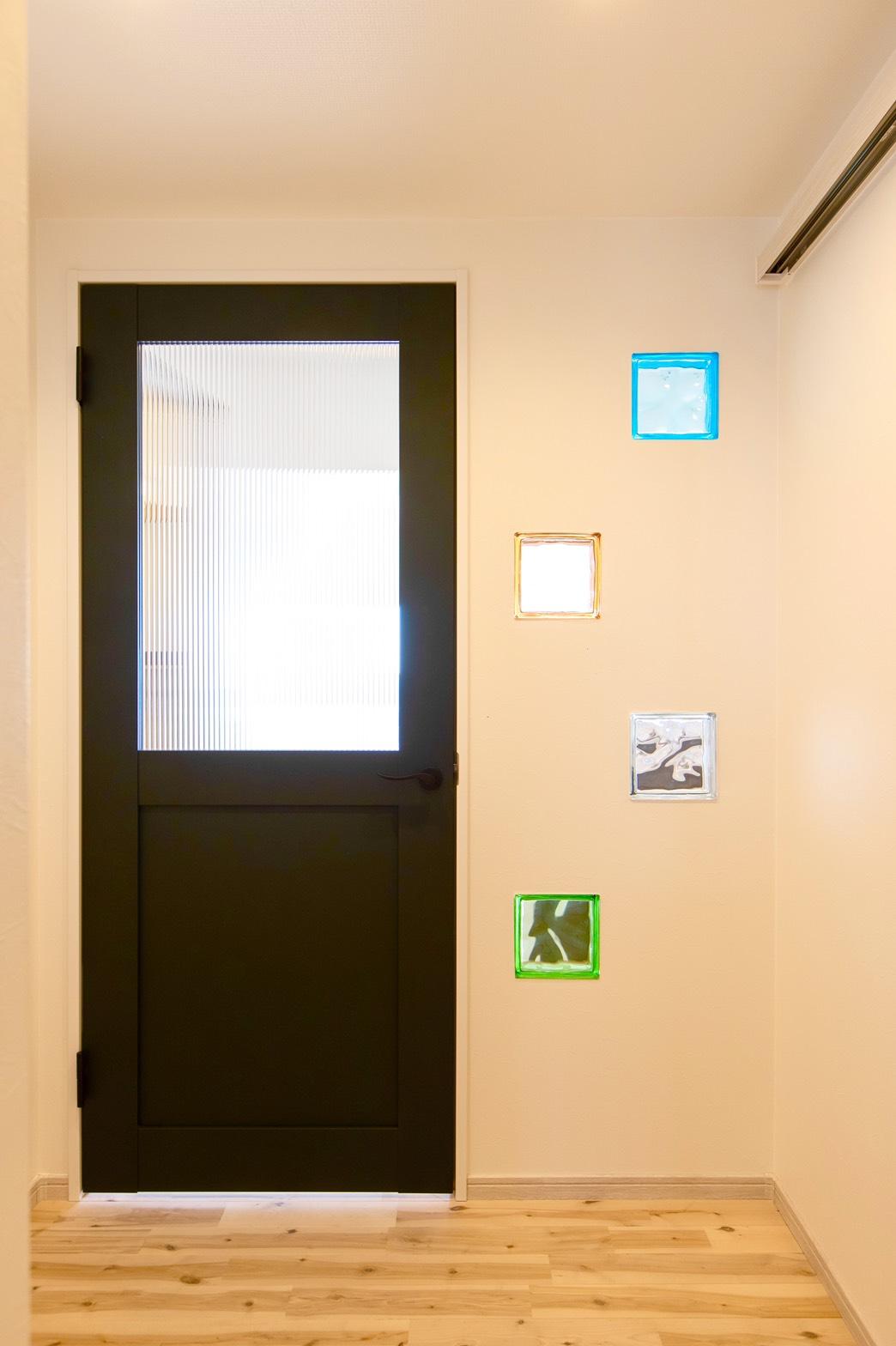 室内ドアの横にカラフルなガラスブロックでアクセント