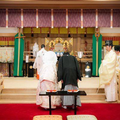 神社の前で礼をする和装の二人旅館宿泊・ウェディング