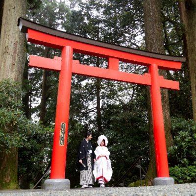 赤い鳥居をくぐる和装の二人・