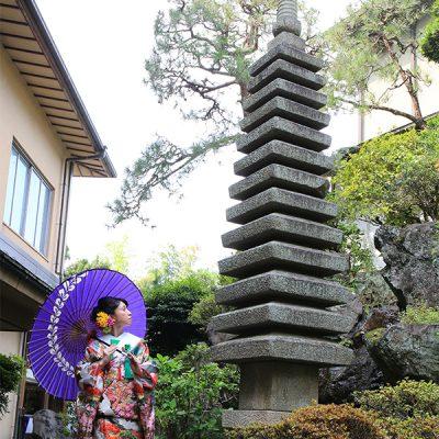 和傘をさしながら塔を見上げる和装花嫁