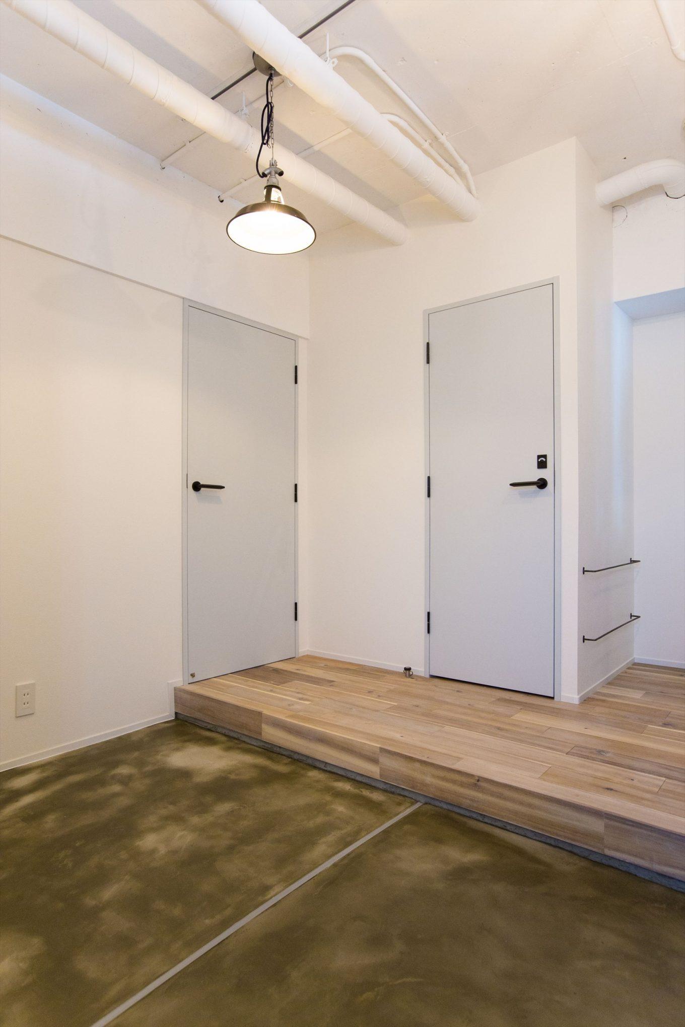 パステルカラーの淡い室内ドアと広い土間