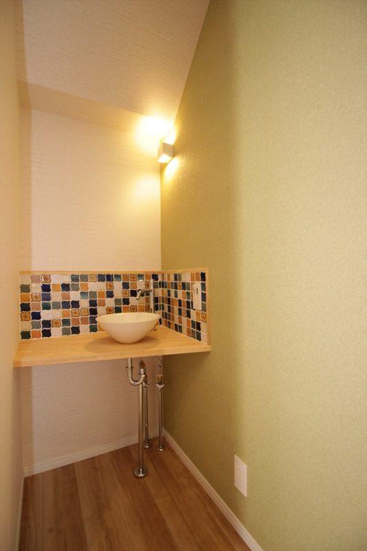 階段下に設けたおしゃれなタイル貼りの手洗いスペース